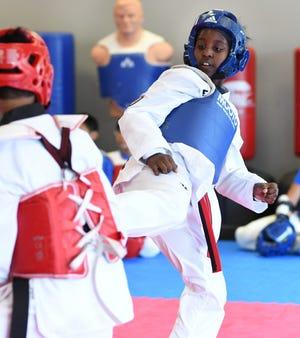 Everest Taekwondo student Leslie Daniels spars with fellow students.