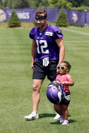 A young fan carries Minnesota Vikings wide receiver Chad Beebe's helmet as he headed to the field.