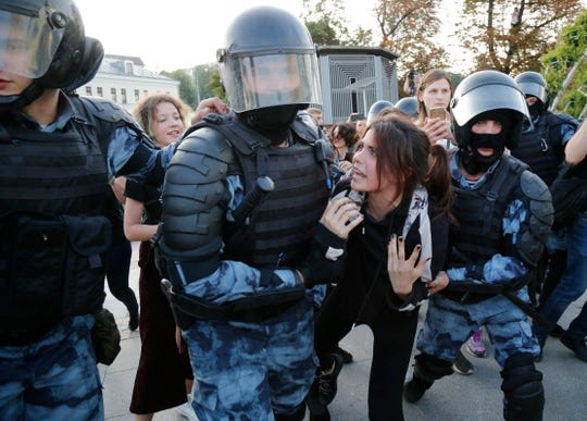 Police officers detain a woman during an unsanctioned rally in the center of Moscow, Russia, on Saturday.