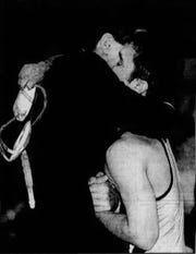 Great Falls High head coach Mike Ranieri hugs Aaron Hartnell after a victory in the 112-pound state finals in 1999.