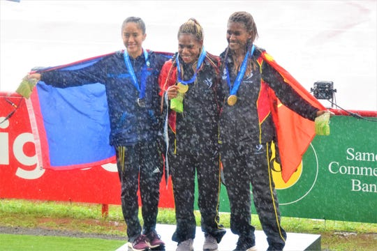 Genina Criss, at left, celebrates at the Apia Park stadium. Criss took the silver medal in the 1500 meter run at the XVI Pacific Games in Samoa.