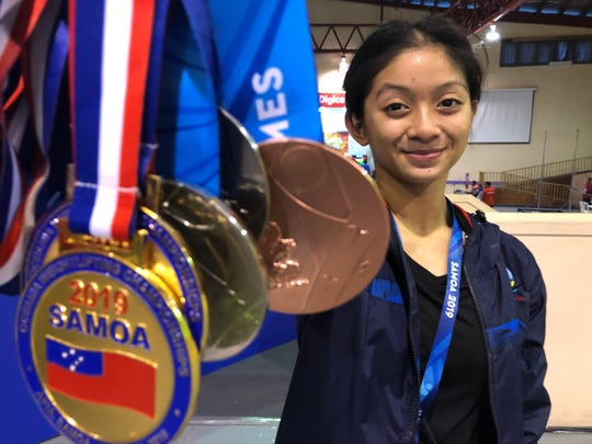 Dayamaya Calma displays her Pacific Games medals behind other medals earned at the XVI Pacific Games in Samoa. Calma got two silver medals for the snatch and total weight, and the bronze for the clean and jerk in the 49 kilo division.