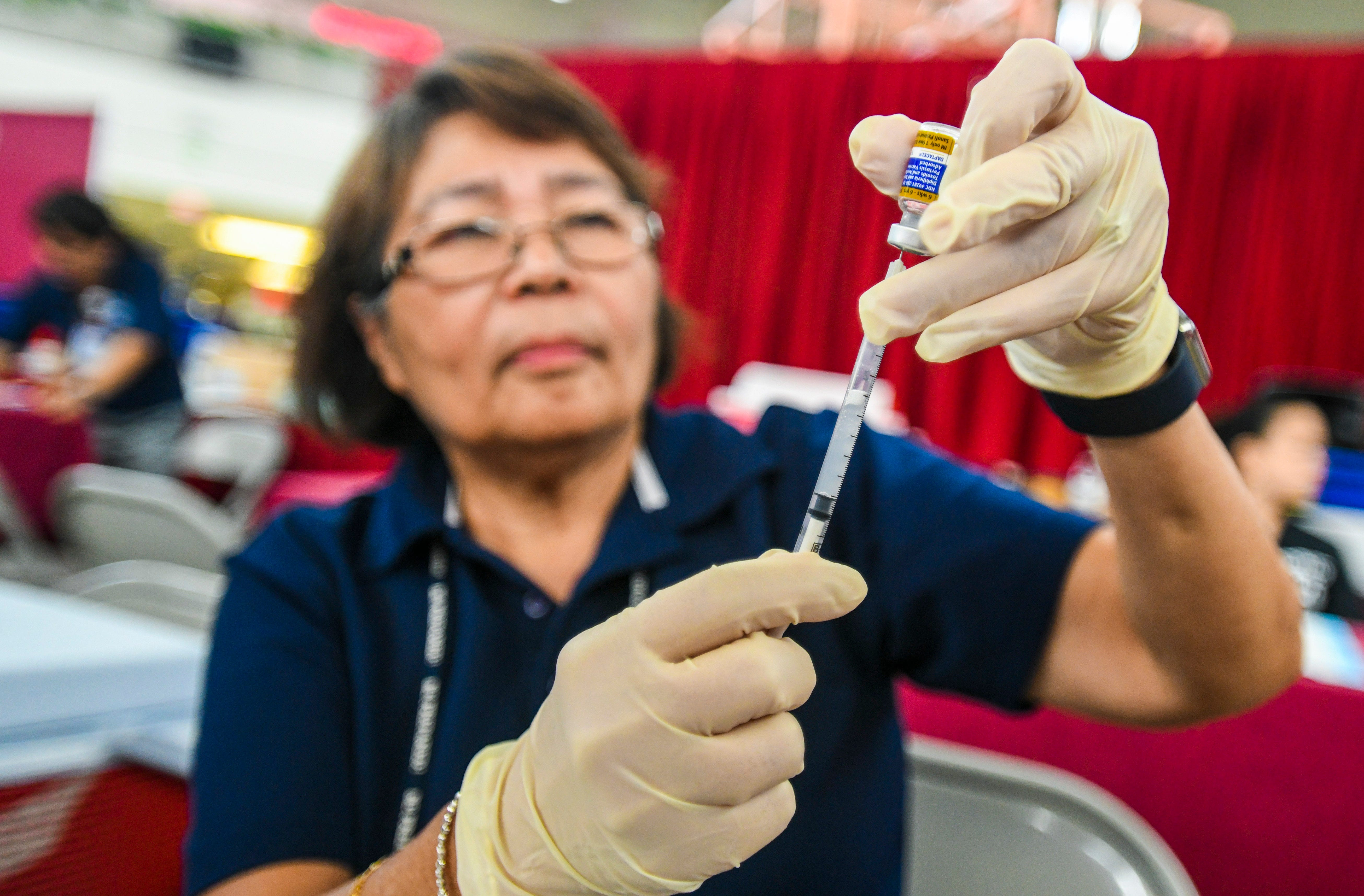 Department of Public Health and Social Services nurse Eva Losbanes draws vaccine from a vial as she prepares loaded syringes at the agency's Back To School immunization clinic at the Micronesia Mall in this July 27 file photo.