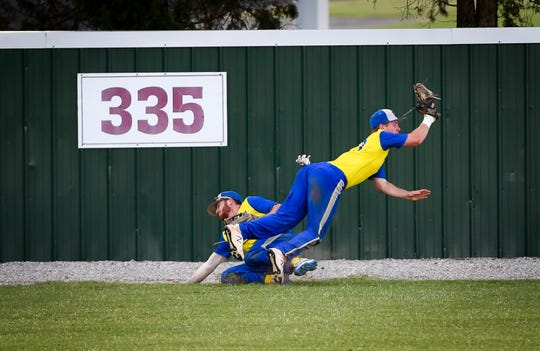Henderson Flash's Trey Hutchison (8), left, and Henderson Flash's Austin Domer (23) get the catch, but collide in the outfield as the Henderson Flash play the Franklin Duelers, at B .T Wayne Field, in the first of a three game series in the Ohio Valley League playoffs Friday, July 26, 2019.