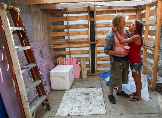 David Walston and girlfriend Amanda Bradshaw have built a small home made from discarded lumber, pallets and wood in the woods near Silver Creek in New Albany. Floyd County officials said they have halted plans to clear what advocates call a quiet area that is home to six full-time residents. But the couple's space, plus the fate of six others who live nearby in the woods, could still face eviction. July 27, 2019
