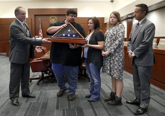 "U.S. Marshals John Garrison, left, and Richard Taylor, right, present a folded flag to Gary Hulsey, his wife Jessica and daughter Summer, all residents of Wylie, Texas, during a ceremony at the United States Courthouse in Plano, Texas, Friday, July 26, 2019. Judges and senior officials with the U.S. Marshals Service gathered at the North Texas courthouse to present the flag and other items to the great, great, great grandson of Marshal Russell Wireman, who was shot in the chest in 1889 during the so-called ""Moonshine War."" (AP Photo/Tony Gutierrez)"