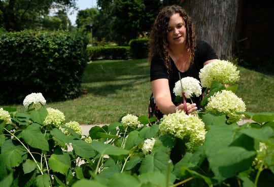 Waverly teacher Nicole Haney cuts flowers Friday, July 26, 2019 from her garden. She arranges them and places the vases on her porch so her neighbors can leave a donation to help kids at the border.