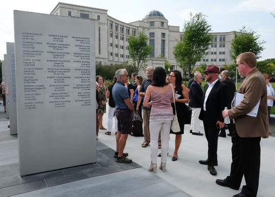 People gather around the Sentinels with the names of law enforcement officers who have died in the line of duty at the Michigan Law Enforcement Officers Memorial Monument Dedication and Memorial Service Saturday, July 27, 2019 in Lansing, Michigan.