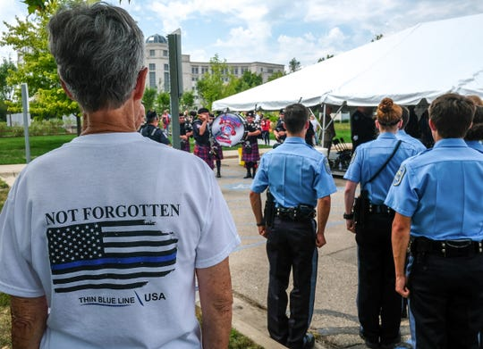 People stand as the Metro Detroit Police and Fire Pipes and Drums play during the dedication of the Michigan Law Enforcement Officers Memorial Monument on Saturday, July 27, 2019 in Lansing, Michigan.