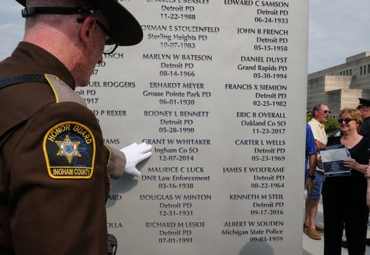 Ingham County Sheriff Deputy Matt Hutting touches the name of Grant W. Whitaker who died in the line of duty in December 2014 at the Michigan Law Enforcement Officers Memorial Monument Dedication and Memorial Service Saturday, July 27, 2019 in Lansing, Michigan.