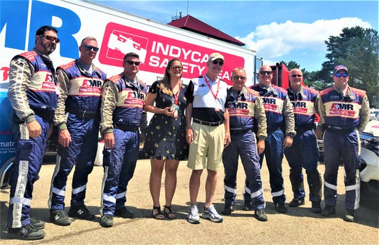 Gerry Schroeder, center, and his daughter, Kathryn, pose with members of the AMR Safety team who saved Gerry's life last year when he collapsed in pit lane due to cardiac arrest at the Honda Indy 200 at Mid-Ohio. In 2019, he made his return to Mid-Ohio to express his gratitude.