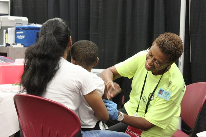 Betsy Robinson of the Shelby County Health Department prepares to give a child his immunizations on July 27, 2019 at Mississippi Boulevard Christian Church.