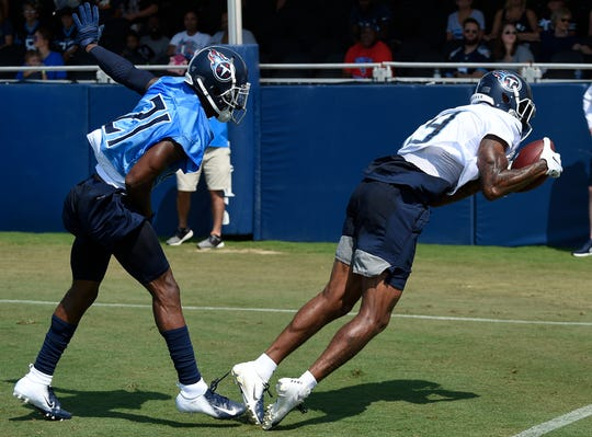 Titans wide receiver Tajae Sharpe (19) pulls in a catch over cornerback Malcolm Butler (21) during practice at Saint Thomas Sports Park Saturday, July 27, 2019, in Nashville, Tenn.