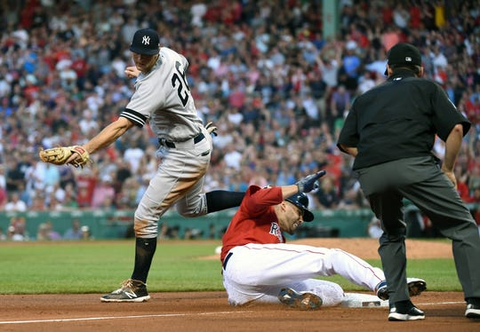 Jul 26, 2019; Boston, MA, USA; Boston Red Sox designated hitter J.D. Martinez (28) safely slides underneath the tag of New York Yankees third baseman DJ LeMahieu (26) during the third inning at Fenway Park.