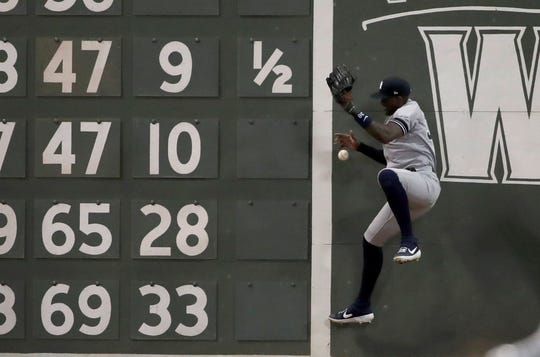New York Yankees left fielder Cameron Maybin jumps but can't make the play on an RBI double off the wall by Boston Red Sox's Sam Travis in the seventh inning of a game at Fenway Park, Friday, July 26, 2019, in Boston.