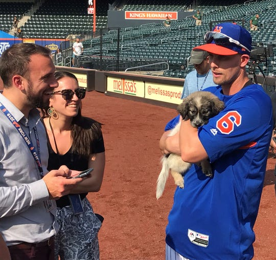 Jeff McNeil, right, holds what turns into his new pet, Friday as the New York Mets had invited North Shore Animal League America to bring some rescues to Citi Field prior to a game against Pittsburgh. McNeil made the adoption official Saturday.