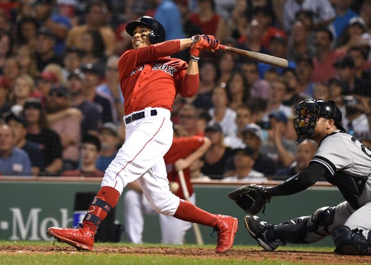 Jul 26, 2019; Boston, MA, USA; Boston Red Sox right fielder Mookie Betts (50) hits his third home run of the game during the fourth inning against the New York Yankees at Fenway Park.