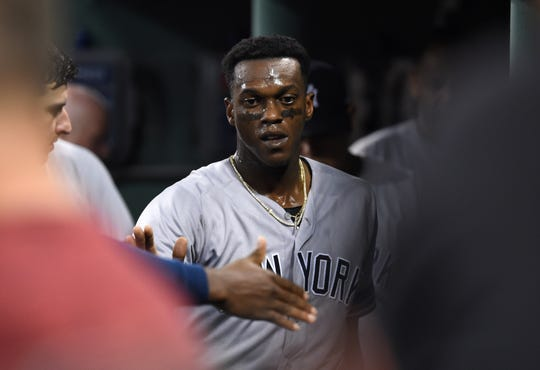 Jul 26, 2019; Boston, MA, USA; New York Yankees left fielder Cameron Maybin (38) is greeted in the dugout after scoring a run during the seventh inning against the Boston Red Sox at Fenway Park.