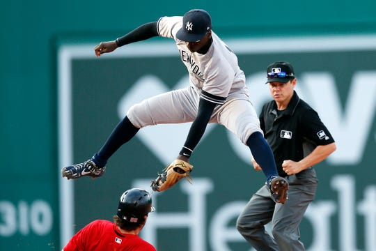 New York Yankees' Didi Gregorius comes down with the high throw as Boston Red Sox's Sam Travis, bottom, steals second base during the sixth inning of a game in Boston, Saturday, July 27, 2019.