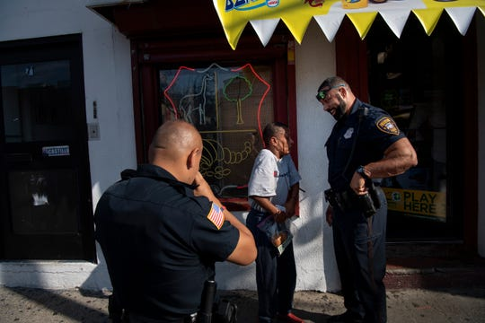 """Paterson Police Officer Ramy Amir talks with a woman while responding to an """"unwanted guest"""" call at a bakery on Market Street on Wednesday, July 24, 2019. (left) Paterson Police Officer Emilio Luque."""