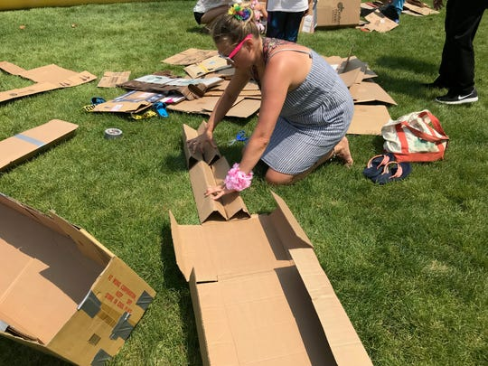 Anna Park of Queens builds a water vessel out of cardboard to compete in the cardboard kayak race in Hoboken on July 27, 2019