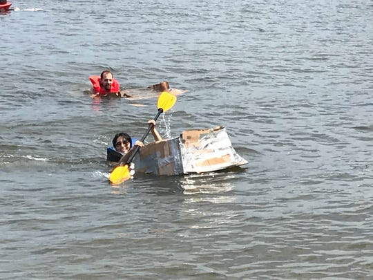 Kirsten Brink, of Weehawken, wins the cardboard kayak race at the Hudson River Cup along the Hoboken shoreline on July 27, 2019.