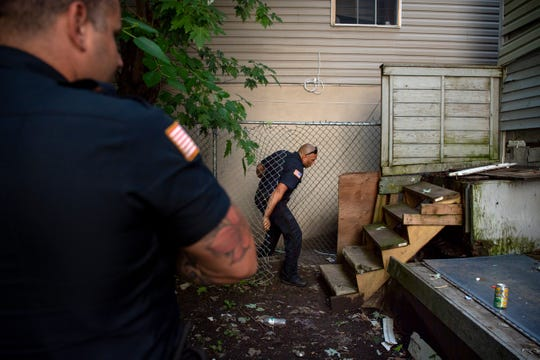 Paterson Police Officers (center) Joshua Serrano and Erick Marino search a property for guns and drugs in the 4th Ward on Wednesday, July 24, 2019.