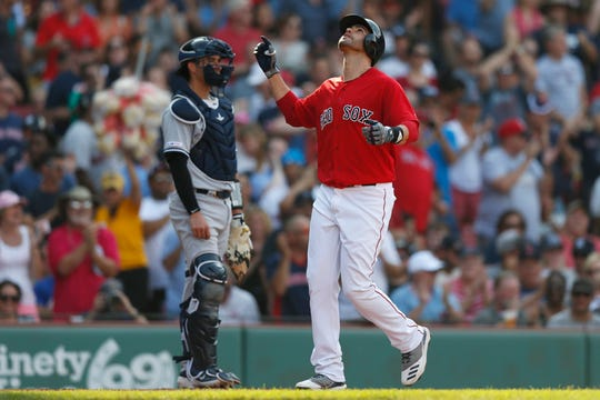 Boston Red Sox's J.D. Martinez celebrates his two-run home run in front of New York Yankees' Kyle Higashioka during the fourth inning of a game in Boston, Saturday, July 27, 2019.
