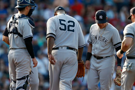 New York Yankees' CC Sabathia leaves the mound after being removed by manger Aaron Boone, behind left, during the fifth inning of a baseball game against the Boston Red Sox in Boston, Saturday, July 27, 2019.