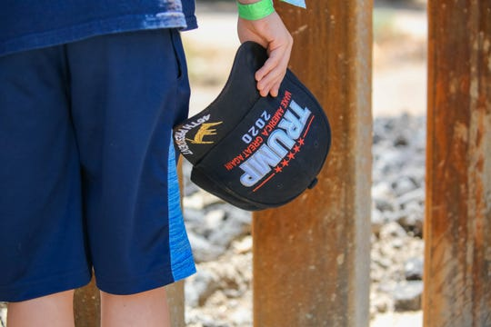 """Joseph Williams holds a Trump cap as he looks through the border wall into Mexico during the """"Symposium at the Wall: Cartels, Trafficking and Asylum,"""" which took place Saturday, July 27, 2019, near the privately builtborder wall in Sunland Park, New Mexico. It was constructed by the WeBuildTheWall organization on American Eagle Brick Co. property."""