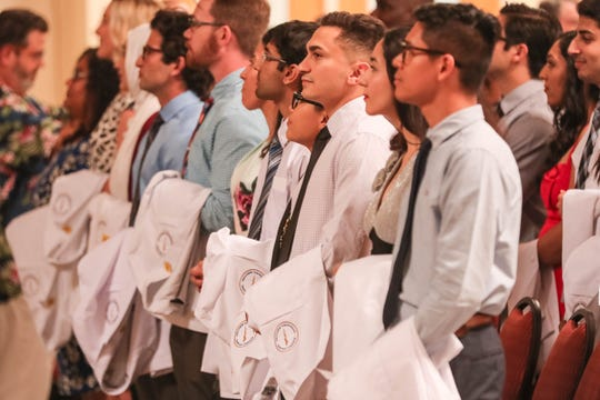 Family and friends wait as students receive their white coats to begin medical school at the white coat ceremony for Burrell College held at the Las Cruces Convention Center in Las Cruces on Friday, July 26, 2019.