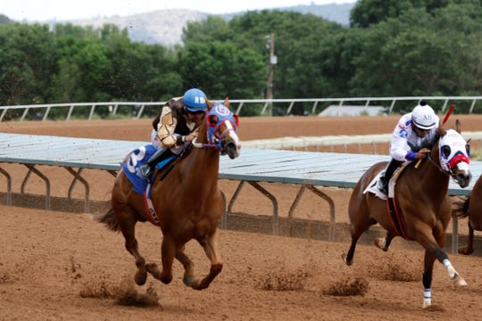 Jess Macho Corona, left, races in the 400-yard quarter horse race at the Ruidoso Down during Zia Fest. Corona won the race with a time of 19.74