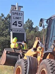 Workers with District 2 New Mexico Department of Transportation install a permanent speed radar sign.