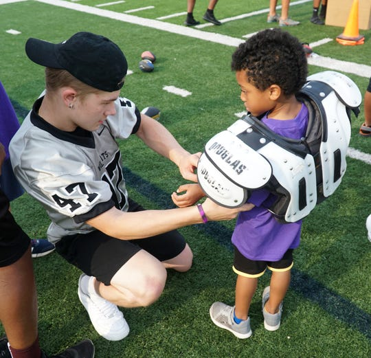 A Sunshine's camper gets his football pads adjusted by a Plymouth Wildcat.