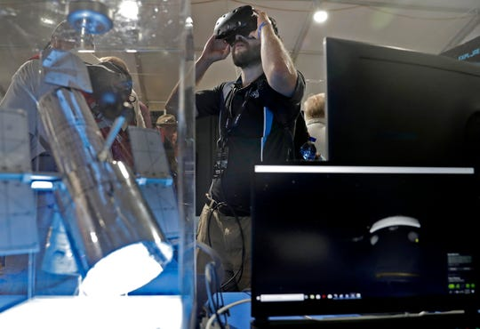 Michael Dunn experiments with a virtual reality simulation of the Hubble telescope in the NASA pavillion during EAA AirVenture Friday, July 26, 2019, at Wittman Regional Airport in Oshkosh, Wis.