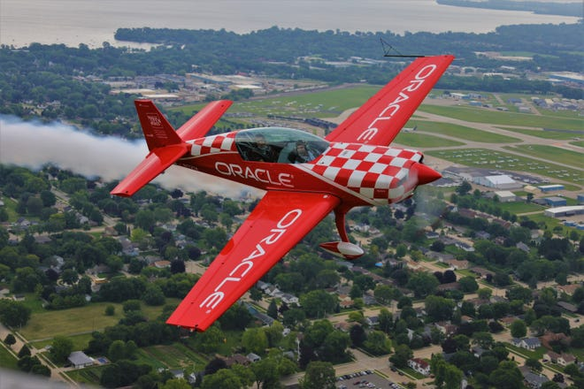 Team Oracle pilot Jessy Panzer produces aerobatic smoke during a flight over Oshkosh during AirVenture 2019.