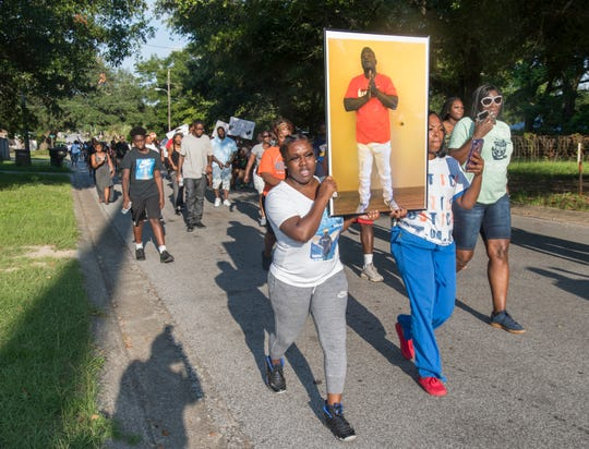 A photo of Tymar Crawford is carried as citizens organized by Dream Defenders march from the site of Crawford's death to the Fricker Center in Pensacola on Friday, July 26, 2019.