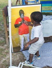 Ka'mare DeLoach, 2, touches a picture of Tymar Crawford as citizens prepare to march from the site of Crawford's death to the Fricker Center organized by Dream Defenders in Pensacola on Friday, July 26, 2019.