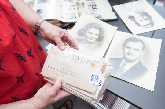 Brittany Mixon holds a stack of WWII love letters between her grandparents Yvonne (née Vanzant) and Clayton Franklin in Pensacola on Thursday, July 25, 2019.  Chelsea Parker and her boyfriend Jason Boatwright bought the letters at a local antique shop and tracked down the Franklins' grandchildren to return the letters which were mistakenly sold at a garage sale.
