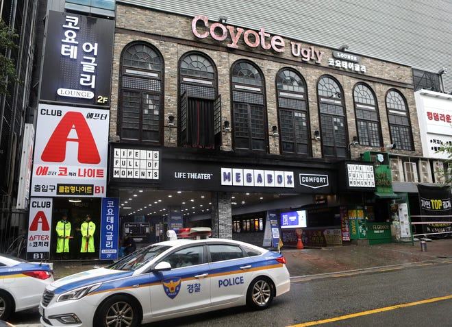 Police stand at the door to a nightclub in Gwangju, South Korea, Saturday, July 27, 2019. Members of the U.S. national water polo team were in a South Korean nightclub on Saturday when an internal balcony collapsed, killing at least one person. A local news agency has reported that one person has died, with 13 injured. No U.S. swimmers were at the club at the time. (AP Photo/Lee Jin-man)