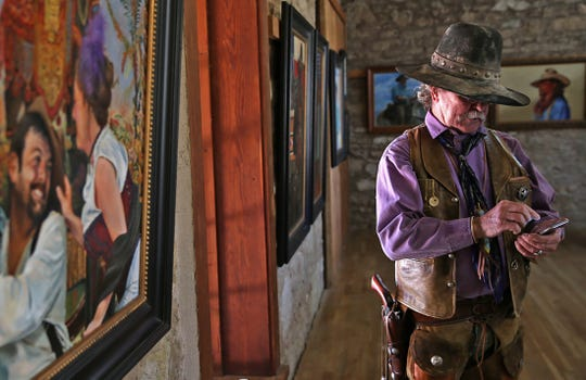 Mike Thompson checks his phone while surrounded by paintings in the American Plains Artists Special Summer Show during the National Cowboy Day event at Fort Concho on Saturday, July 27, 2019.