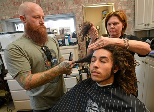 Captain Shreve senior Jared Browning has his hair removed by Jeremy Hurst and Patty Remedies at Shreveport's Shreve Towne Barber Shop.