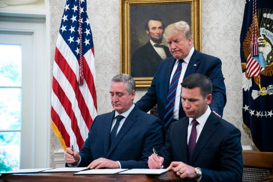 President Donald Trump looks on as acting Homeland Security Secretary Kevin McAleenan and Guatemalan Interior Minister Enrique Degenhart sign a deal to limit asylum claims from Guatemala in the Oval Office of the White House in Washington, D.C, on July 26, 2019.