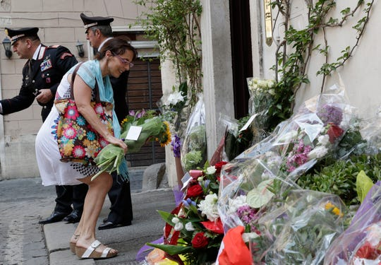 A woman leaves flowers in front of the Carabinieri station where Mario Cerciello Rega was based, in Rome, Saturday, July 27, 2019. In a statement Saturday, Carabinieri officers investigating the death Friday of officer Cerciello Rega, 35, said two American turists, both 19, have been detained for alleged murder and attempted extortion. (AP Photo/Andrew Medichini) ORG XMIT: ROM102