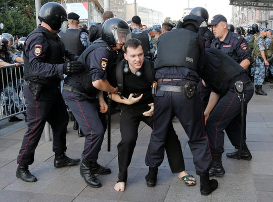 Police officers detain a man during an unsanctioned rally in the center of Moscow on July 27, 2019. Russian police are wrestling with demonstrators and have arrested hundreds in central Moscow during a protest demanding that opposition candidates be allowed to run for the Moscow city council.