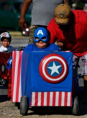 Jose Dominguez, 4, gets a push as he drives his Captain America-themed cardboard car during Saturday's Main Street Lawn Car Show in Lawn. The Cardboard Car Parade encouraged participants to use their imaginations to fashion a fantasy ride from a box.