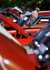 Judges and car show visitors wander between the open hoods of classic cars at the Main Street Lawn Car show in Lawn on Saturday.