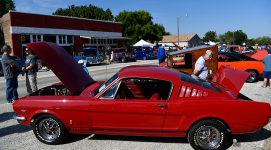 Mike Mitchell evaluates a 1966 Ford Mustang Fastback during Saturday's Main Street Lawn Car Show in Lawn.