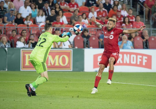 Jul 27, 2019; Toronto, Ontario, CAN; Toronto FC midfielder Nick DeLeon (18) battles for a ball with FC Cincinnati goalkeeper Przemyslaw Tyton (22) during the first half against FC Cincinnati at BMO Field.