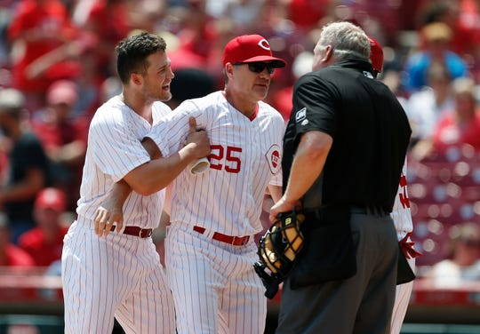 Cincinnati Reds manager David Bell (25) holds back Nick Senzel, left, just after Senzel was ejected from the game by home plate umpire Bill Miller, right, arguing a third strike call during the fourth inning of a baseball game against the Colorado Rockies, Sunday, July 28, 2019, in Cincinnati.
